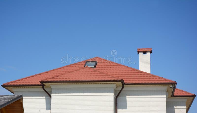 Tejado de la arcilla roja de la casa con el tragaluz del ático, la chimenea, el canal del tejado y el espacio de la copia foto de archivo libre de regalías