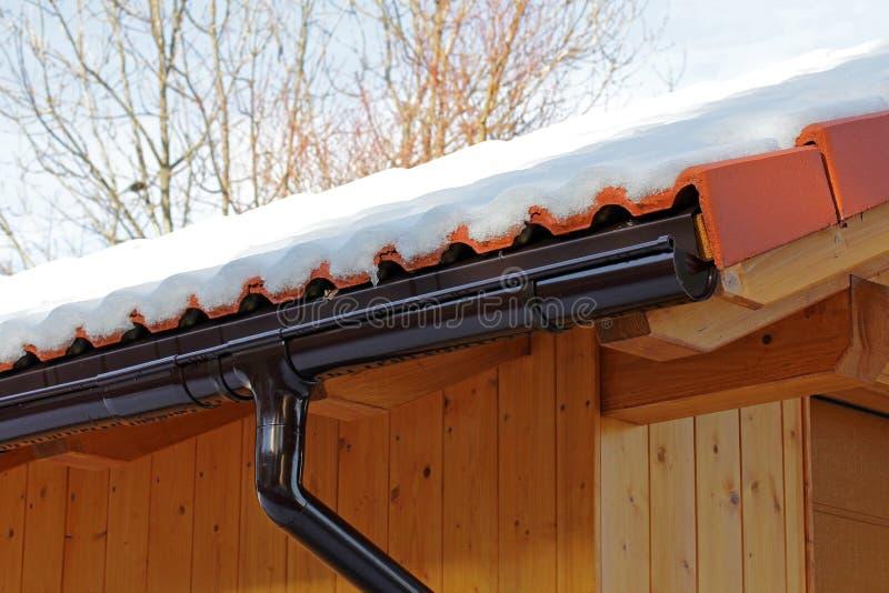 Tejado de madera con el canal de la lluvia y tubo de drenaje en invierno foto de archivo