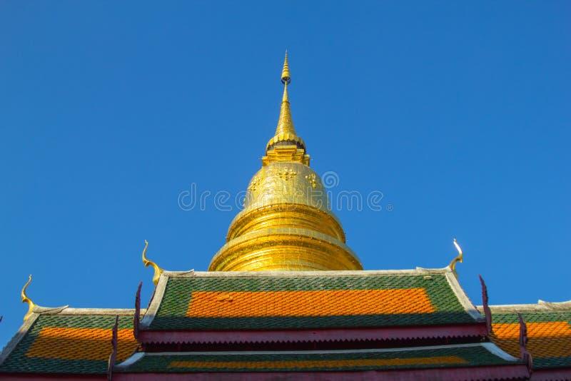 Tejado de oro de la pagoda y del templo en templo tailandés con el fondo del cielo azul imagenes de archivo