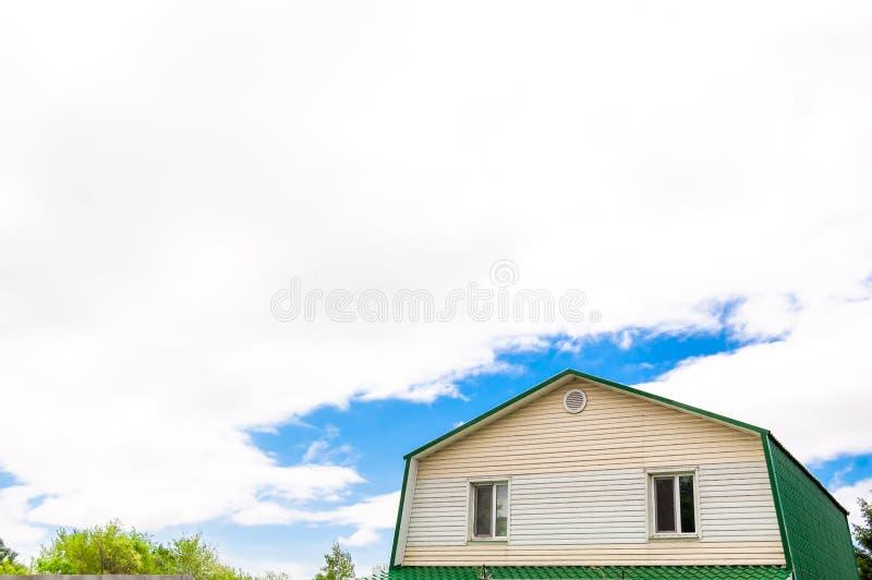 Tejado del ático con dos ventanas en la casa contra el cielo azul con las nubes fotografía de archivo