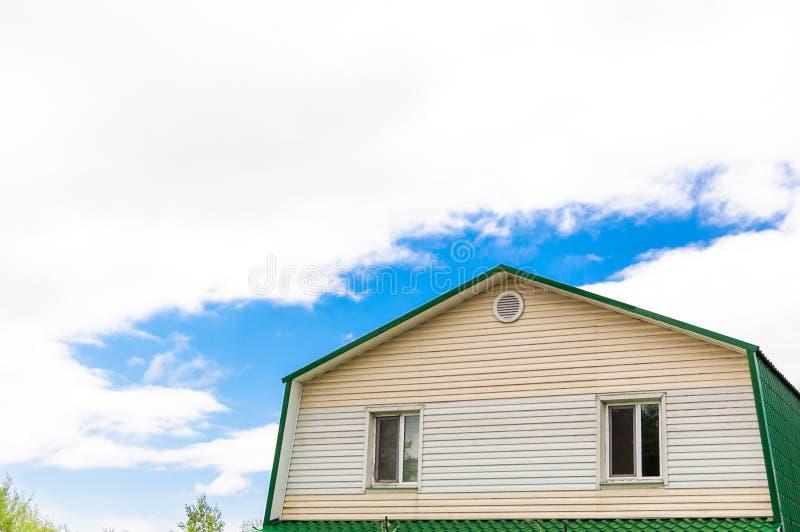 Tejado del ático con dos ventanas en la casa contra el cielo azul con las nubes imagen de archivo