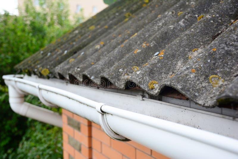 Tejado del amianto de la casa con cierre encima del tenedor del canal y del tubo plástico del canal del tejado guttering imágenes de archivo libres de regalías