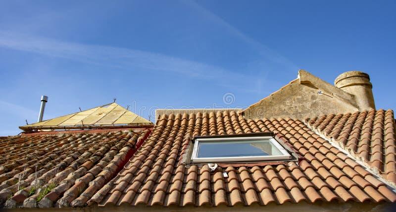 Tejado en tejas de la terracota con el tragaluz imágenes de archivo libres de regalías