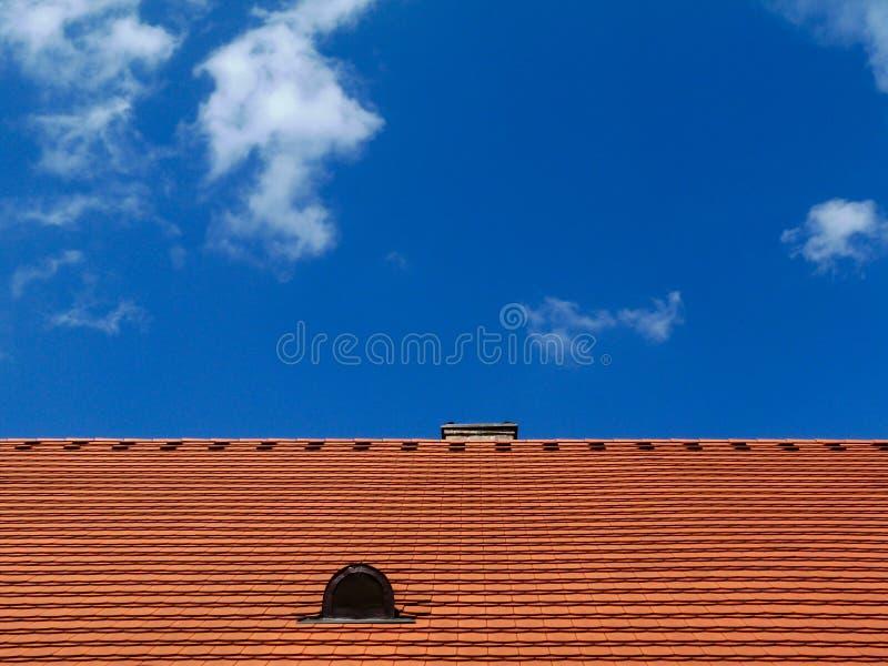 tejado inclinado rojo marrón moderno de la arcilla con el respiradero debajo del cielo azul imagenes de archivo