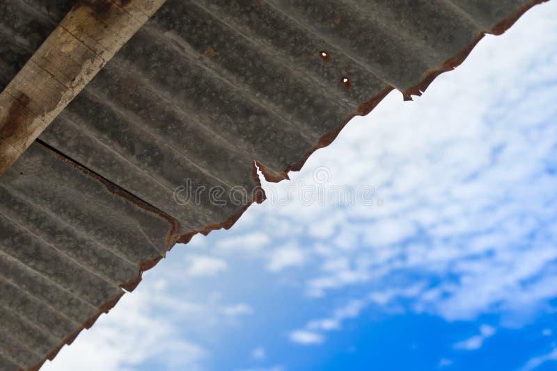 Tejado oxidado viejo del cinc con nublado foto de archivo libre de regalías