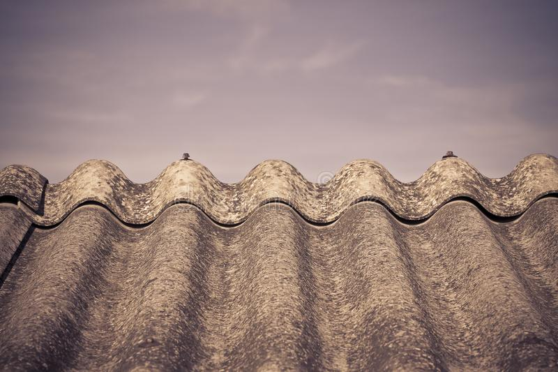 Tejado peligroso envejecido viejo hecho de los paneles concretos - un o del amianto fotografía de archivo