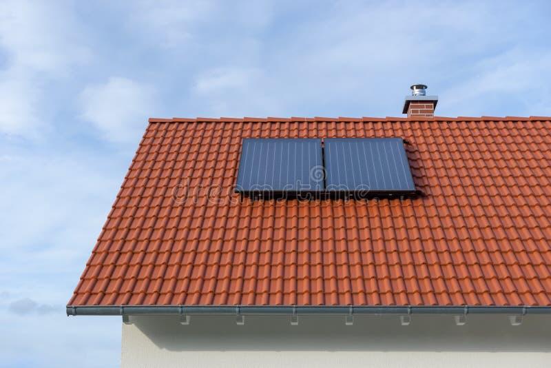 Tejado tejado rojo con la central térmico solar fotografía de archivo