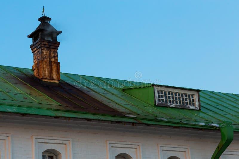Tejado verde de la lata con la chimenea sucia con las manchas de la lata imagen de archivo libre de regalías