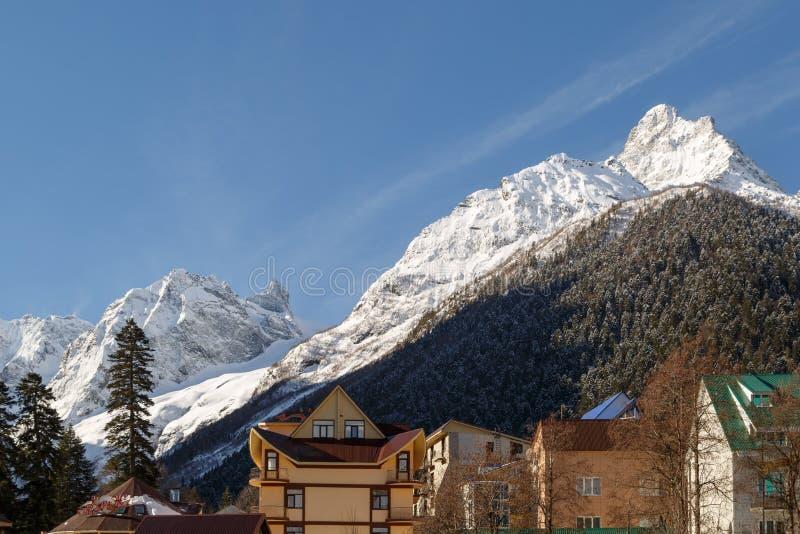 Tejados de casas y de hoteles en el fondo de montañas coronadas de nieve y de bosques coníferos imperecederos fotos de archivo