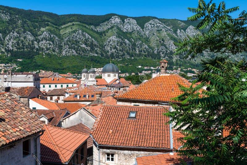 Tejados tejados rojos de las casas de ciudad viejas en Kotor y la iglesia ortodoxa servia de St Nikola, Montenegro fotos de archivo