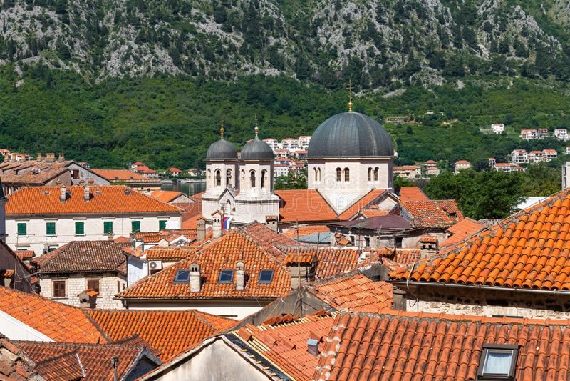 Tejados tejados rojos de las casas de ciudad viejas en Kotor y la iglesia ortodoxa servia de St Nikola, Montenegro imagen de archivo