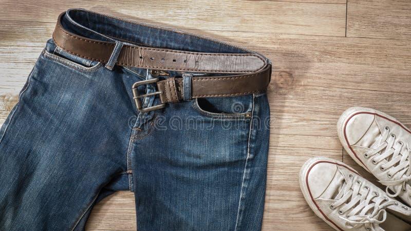 Tejanos con la correa de cuero y los zapatos blancos sucios de la zapatilla de deporte en t foto de archivo libre de regalías