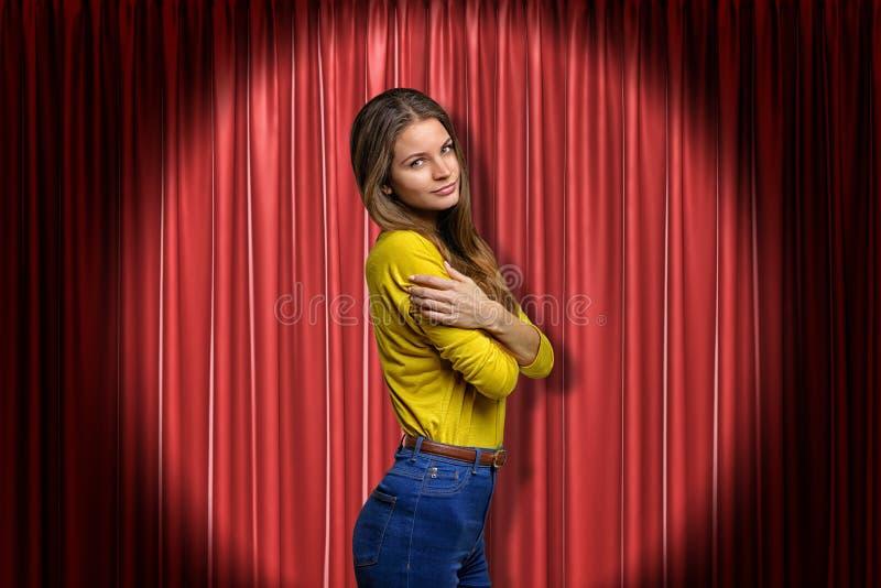 Tejanos que llevan de la mujer joven y camisa amarilla que se abrazan en fondo rojo de las cortinas de la etapa imagen de archivo