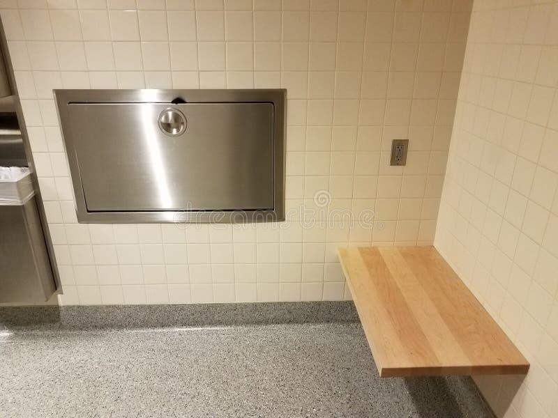 Tejas blancas en cuarto de baño con la estación cambiante de madera del bebé del banco y del metal imagenes de archivo