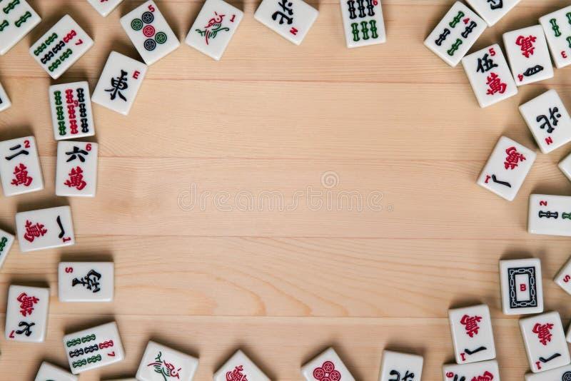 tejas Blanco-verdes para el mahjong en un fondo de la madera marrón clara Espacio vacío en el centro foto de archivo