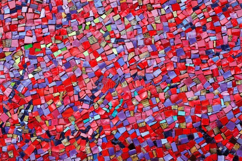 Tejas de mosaico de piedra rojas, rosadas, amarillas, y púrpuras coloridas en la pared imagen de archivo