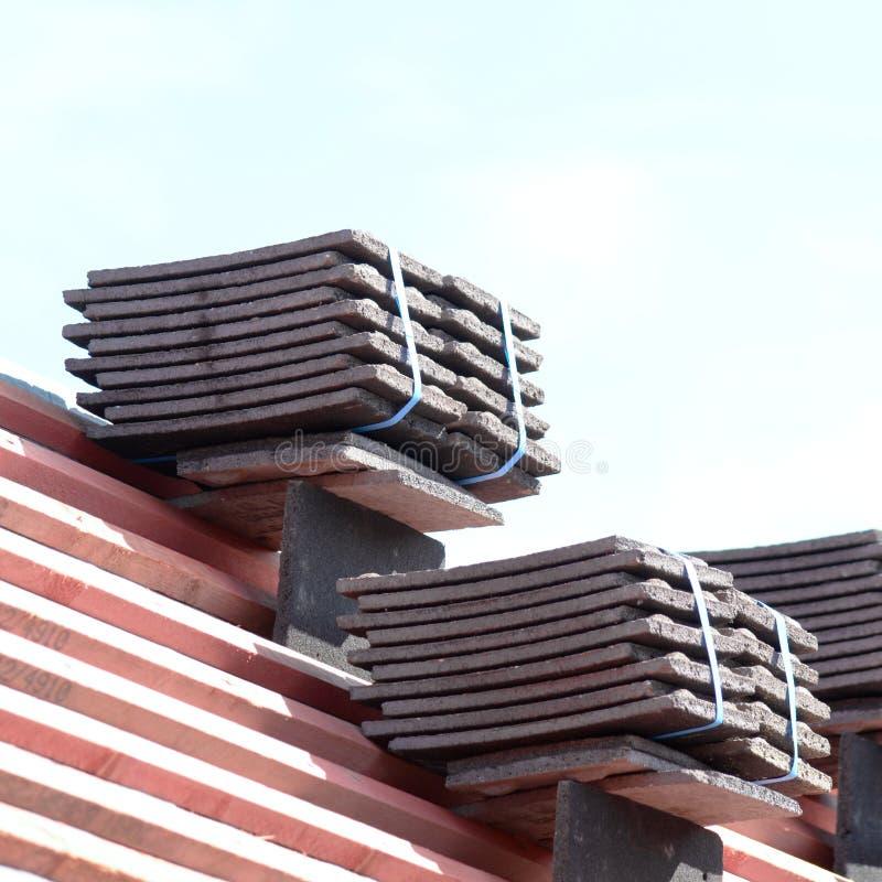 Tejas de tejado apiladas en pilas en los listones de madera foto de archivo