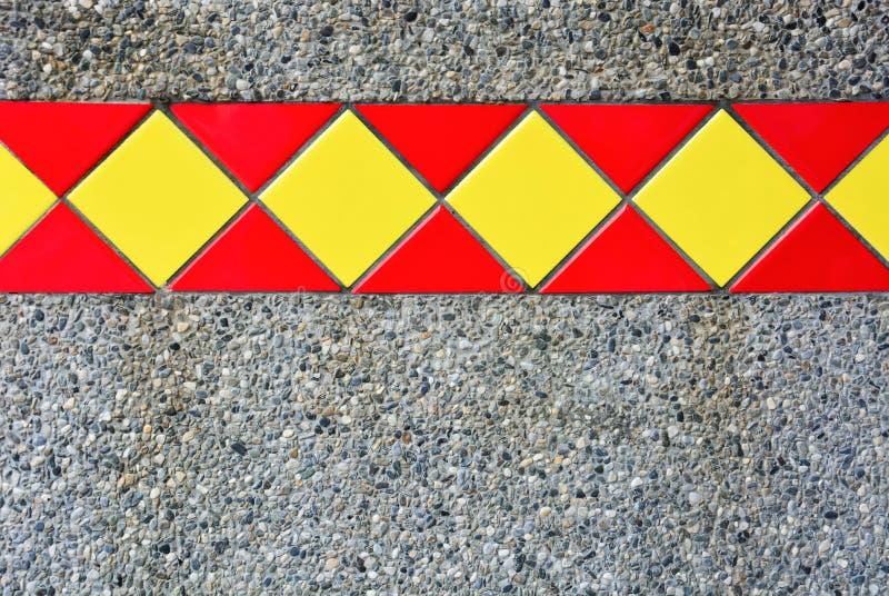 Tejas rojas y amarillas en la arena mezclada con el pequeño fondo de la textura de la pared de piedra fotografía de archivo libre de regalías