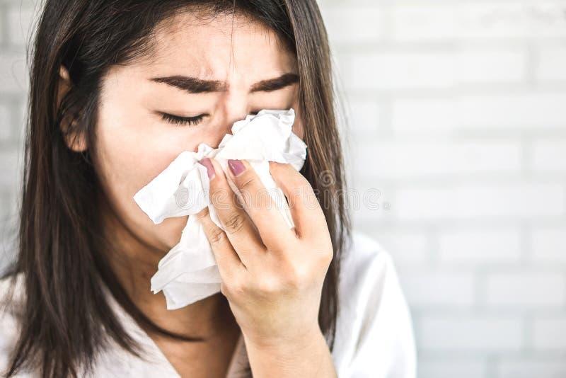 Tejido asiático de la tenencia de la mano de la mujer que estornuda teniendo fiebre y gripe imagen de archivo libre de regalías