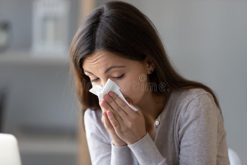 Tejido enfermo de la tenencia de la mujer joven y soplar su nariz corriente imagenes de archivo
