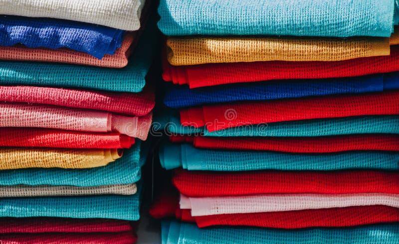Tejidos textiles de fabricación multicolores en pilas imagen de archivo