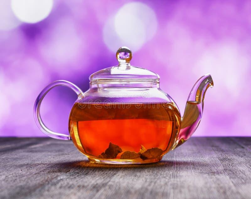 Tekanna av nytt te på purpurfärgad bakgrund arkivbilder