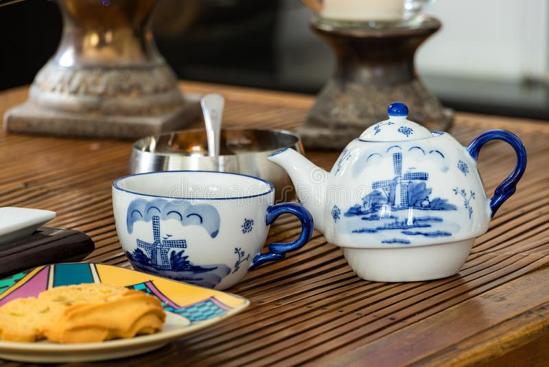 Tekanna och en kopp med socker och kakor på en lantlig kaffetabell, dagljus, inomhus arkivbilder