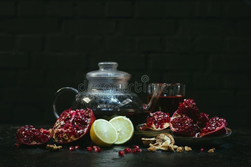 tekanna och exponeringsglas med granatäpplefruktsaft och citroner på a arkivfoto