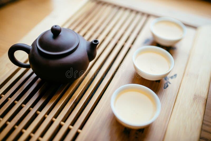 Tekanna och koppar med kinesiskt te på tabellen för teceremonin royaltyfri fotografi