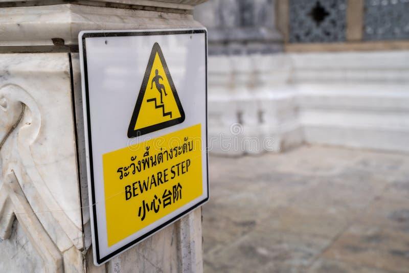 Teken bij het Grand Palace Bangkok Thailand - Engelse vertaling uit Thailand - Beware Step - vertelt bezoekers hun stap te zien stock fotografie