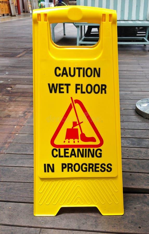 Teken die van de voorzichtigheids het natte vloer lopend teken op houten vloer schoonmaken stock afbeelding
