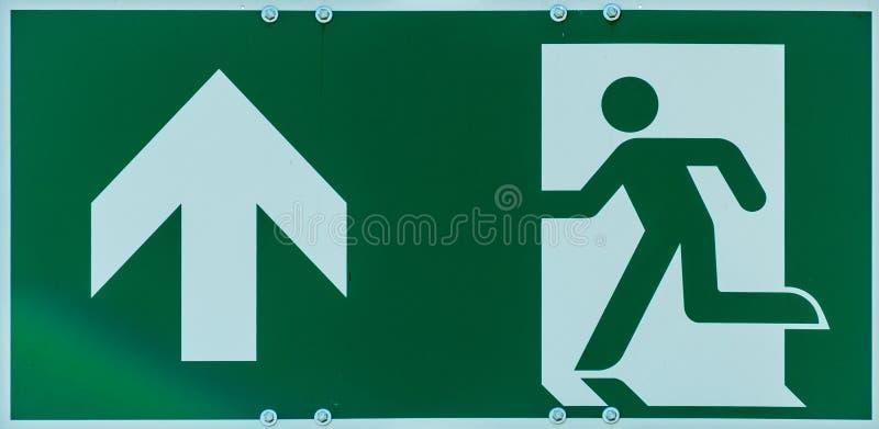 Teken met het pictogram van een lopende persoon en een pijl in wit op een groene achtergrond, aanwijzing van een vluchtroute in h stock fotografie