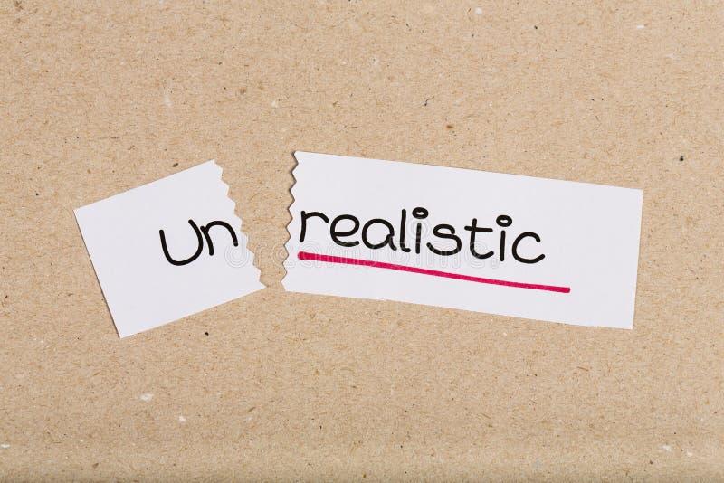 Teken met onrealistisch woord geworden realistisch royalty-vrije stock afbeeldingen