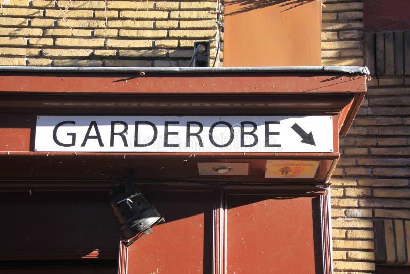 Teken op bakstenen muur bij een restaurant die richting tonen aan de Nederlands/Duitse garderobe: Garderobe stock afbeeldingen