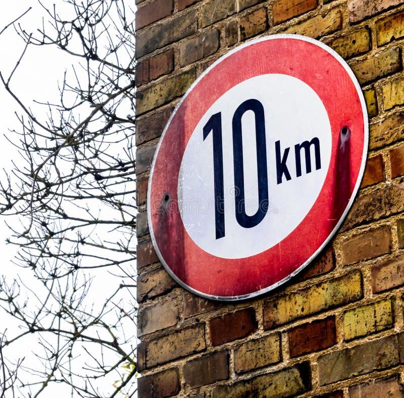 Teken op een muur met gele bakstenen die op de maximum toepasselijke snelheid van 10 kilometers per uur wijzen stock afbeelding