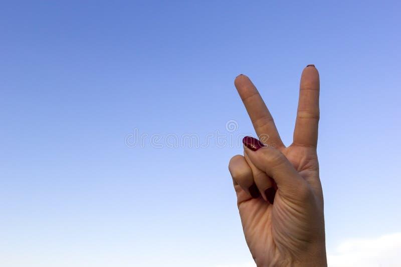 Teken of overwinning van de hand de het gesturing vrede op blauwe hemelachtergrond stock afbeeldingen