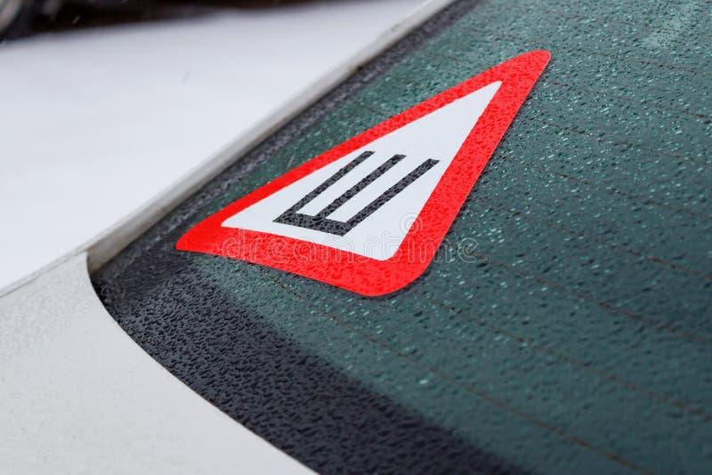 Teken van beslagen banden op het achterruit van de auto Veilige beweging op sneeuw behandelde wegen stock afbeeldingen
