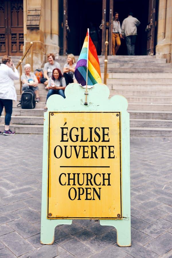 Teken van een vrolijke het bevestigen kerk met een de trotsvlag van de lgbtregenboog op het en groep die mensen bij ingang van de stock afbeelding