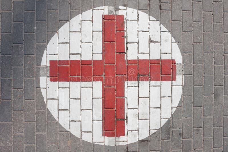 Teken van het medische rode kruis op de stoep stock fotografie