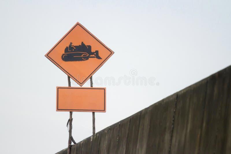 Teken voor de werkende oranje achtergrond van het tractor zwarte symbool stock foto
