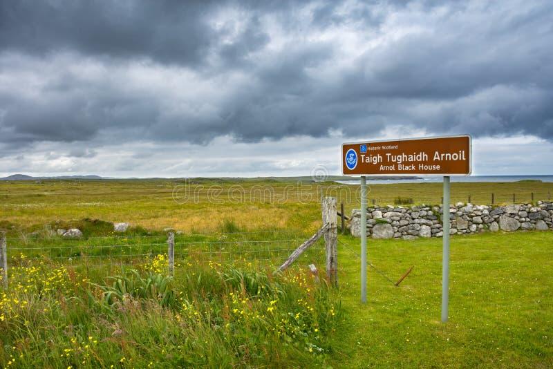 Teken voor het Zwarte Huis van Arnol in Gaëlisch met mooi Schots landschap op de achtergrond stock foto