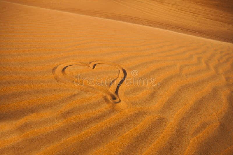 Tekening van romantisch hart in de Arabische zandwoestijn stock fotografie