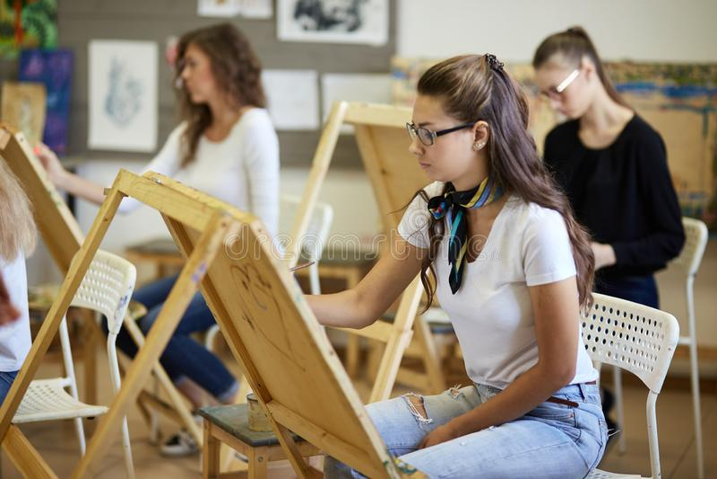 Tekeningsles in de kunststudio Boom die de jonge beelden charmeren die van de meisjesverf bij de schildersezels zitten royalty-vrije stock foto's