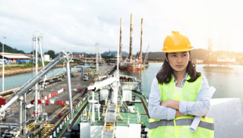 Teknik som bär den gula hjälmen och arbetar på konstruktionsplatsen om trans. av den internationella logistiken royaltyfria bilder