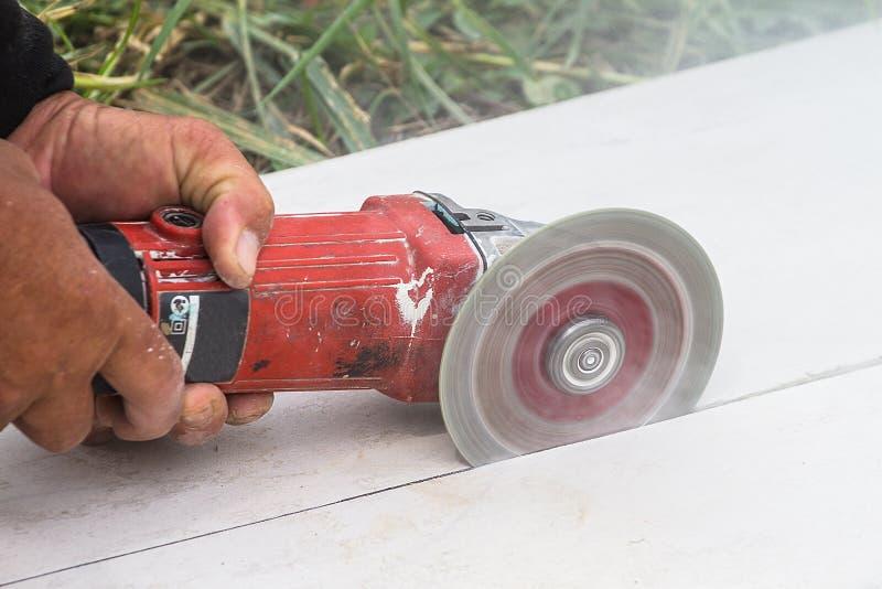 Tekniker använder ark för snitt för en mala maskin för hand av cementbrädet royaltyfri foto