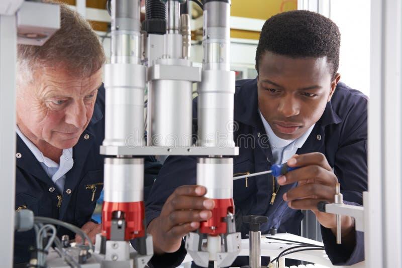 Tekniker And Apprentice Working på maskinen i fabrik royaltyfria bilder