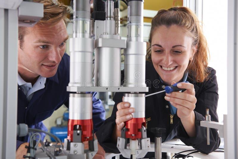 Tekniker And Apprentice Working på maskinen i fabrik royaltyfri bild