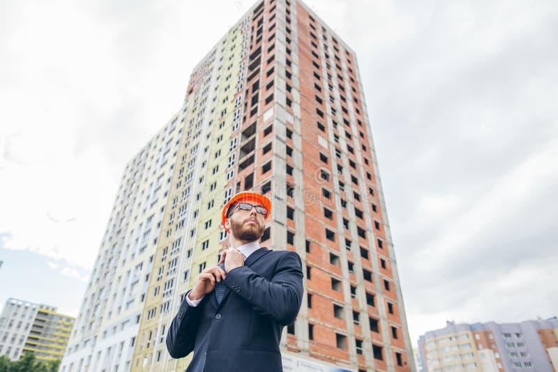 Tekniker byggmästare i hjälm, byggmästare med exponeringsglas på konstruktionsplatsen royaltyfri fotografi