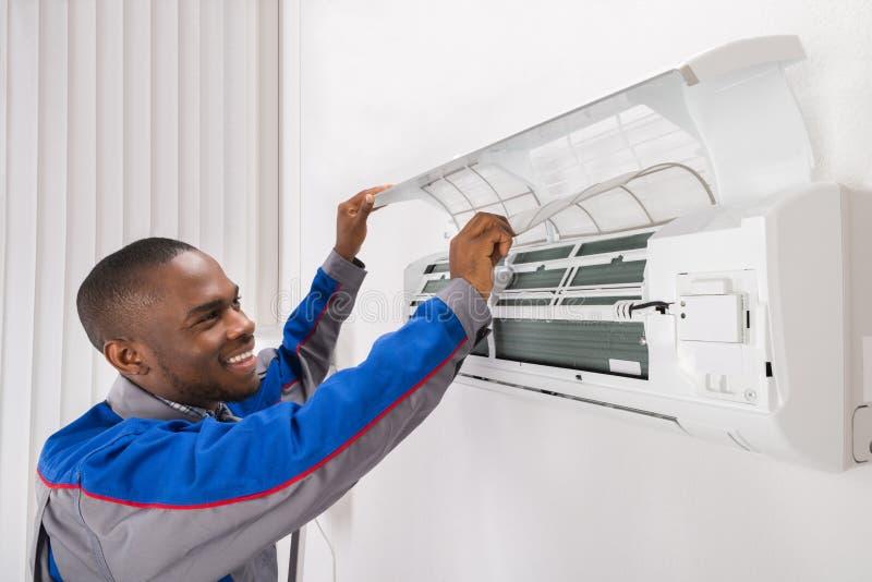 Tekniker Checking Air Conditioner arkivbild