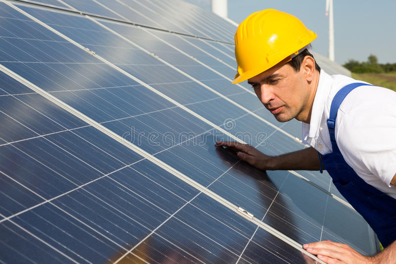 Tekniker eller montör som kontrollerar paneler för sol- energi arkivfoto